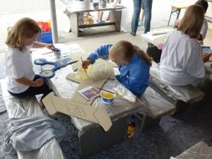 Konzentriert malen die Kinder die Figuren bunt aus.
